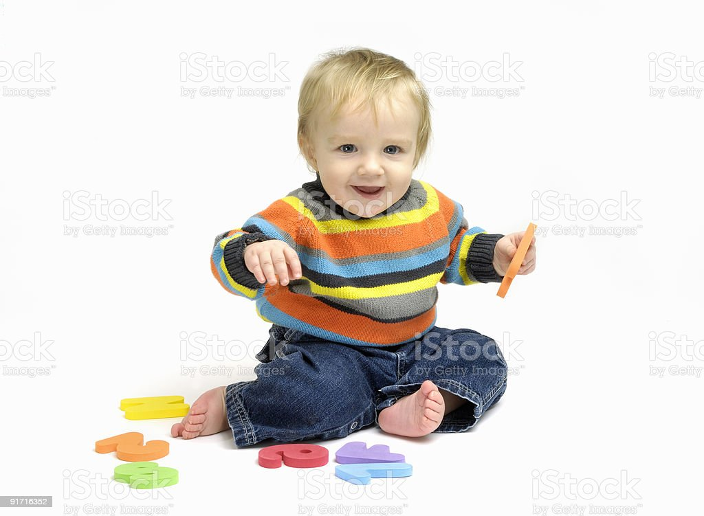 Smiling baby boy playing with numbers and letters royalty-free stock photo