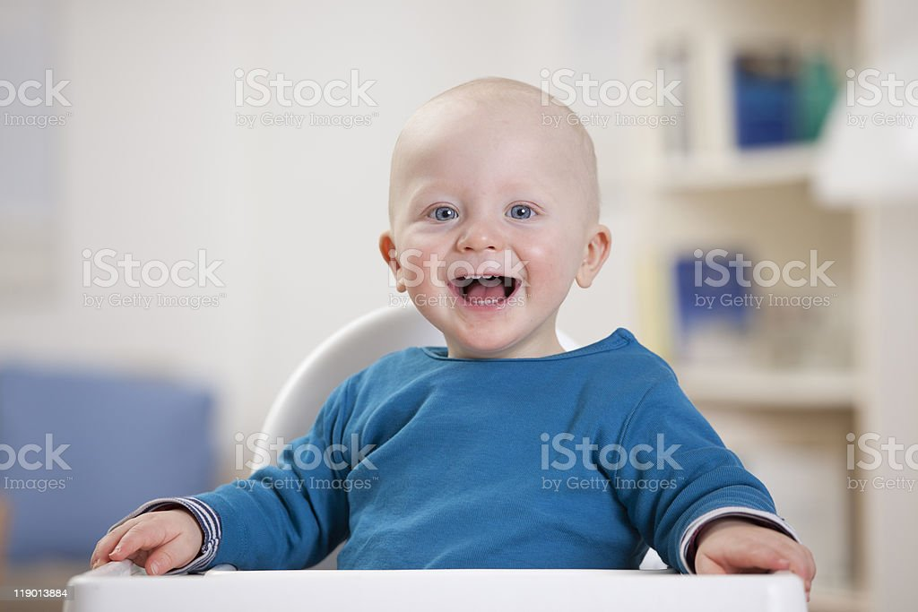Smiling baby boy sitting in high chair stock photo