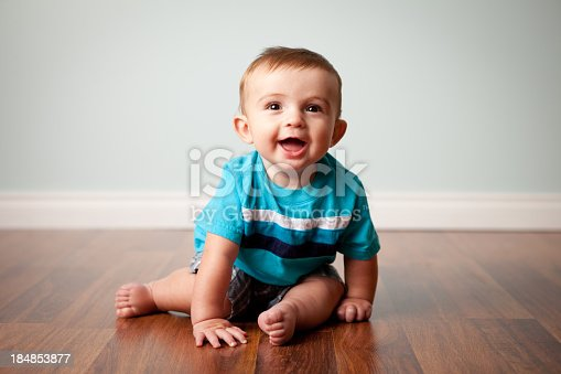 Smiling Baby Boy Sitting on Shiny Hardwood Floor