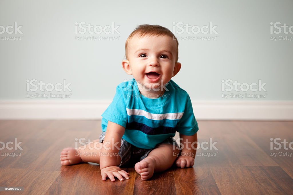 Smiling Baby Boy Sitting on Shiny Hardwood Floor stock photo
