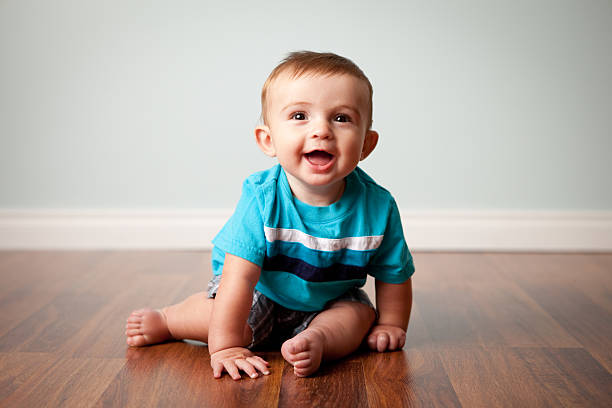 Smiling Baby Boy Sitting on Shiny Hardwood Floor