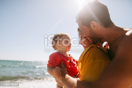 Photo of smiling baby boy with his parents at the beach