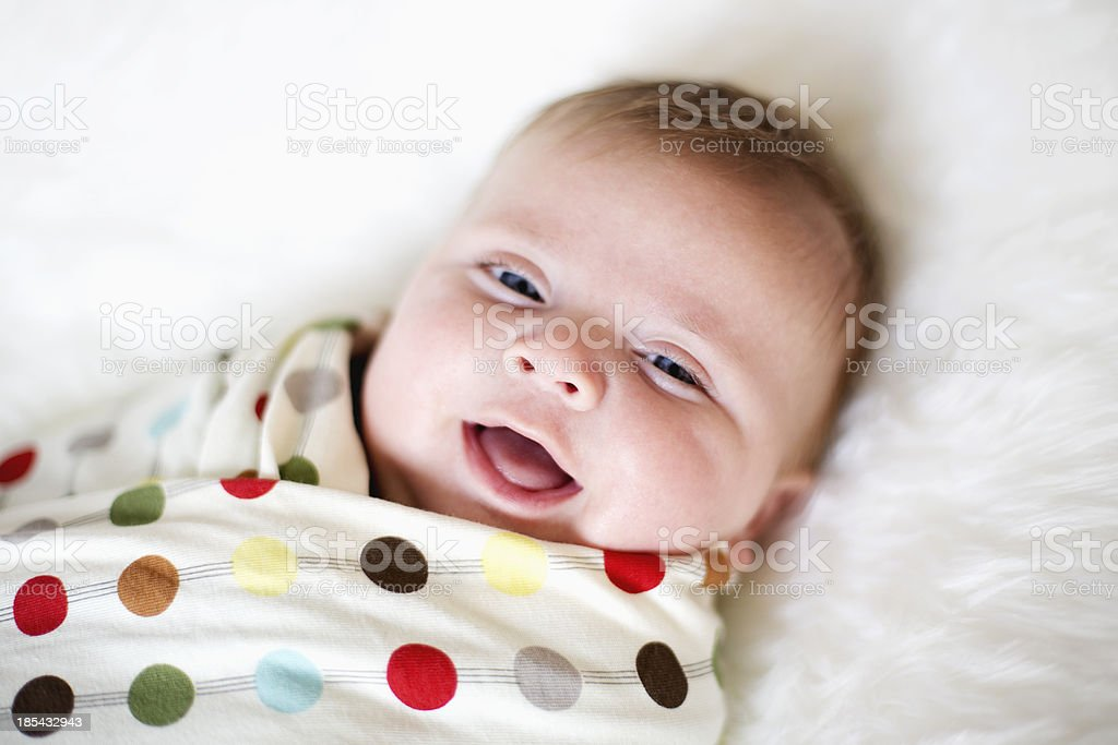 Smiling baby boy, wrapped in a poka-dot blanket stock photo