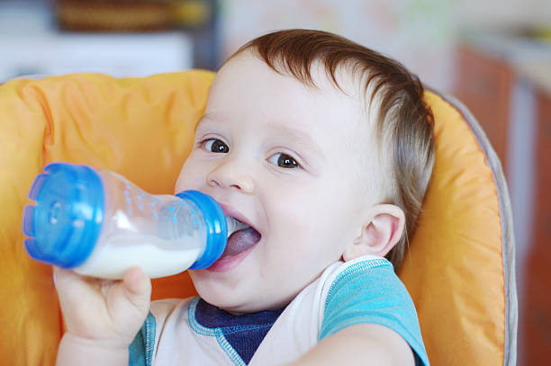 smiling baby drinks milk from a small bottle stock photo