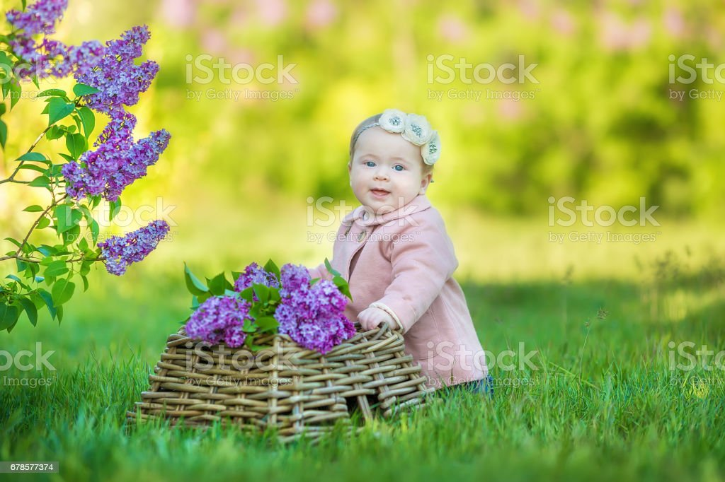 Smiling baby girl 1-2 year old wearing flower wreath, holding bouquet of lilac outdoors. Looking at camera. Summer spring time. – Foto
