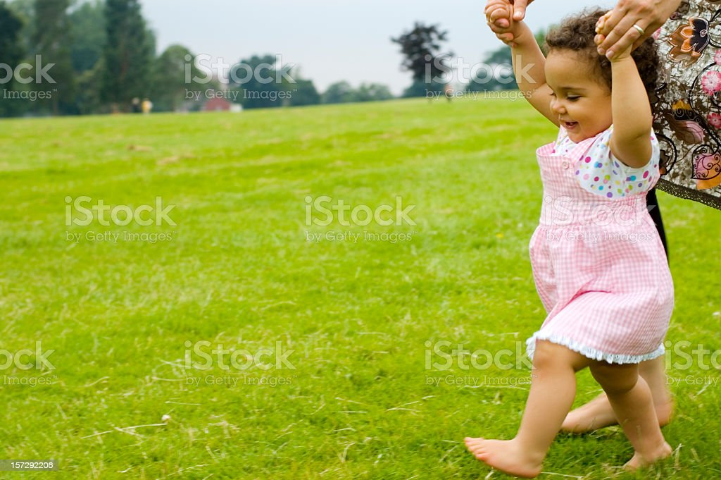 Smiling baby girl learns how to walk on grass with mother  stock photo