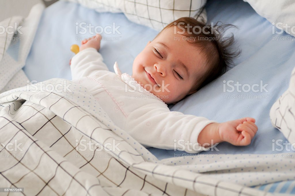 Smiling baby girl lying on a bed stock photo