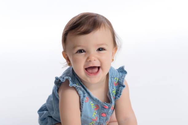 Smiling Baby Girl Wearing a Denim Romper stock photo