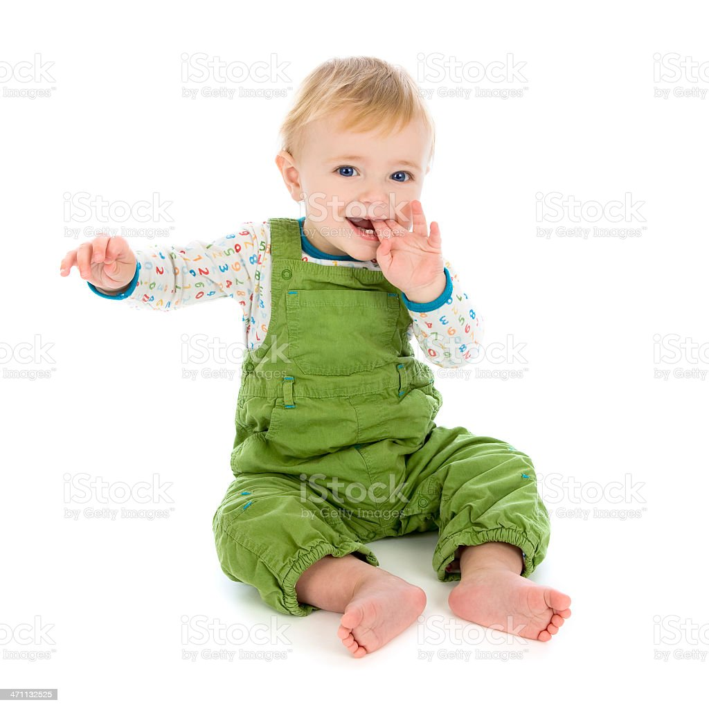 Smiling baby in green dungarees on white background stock photo