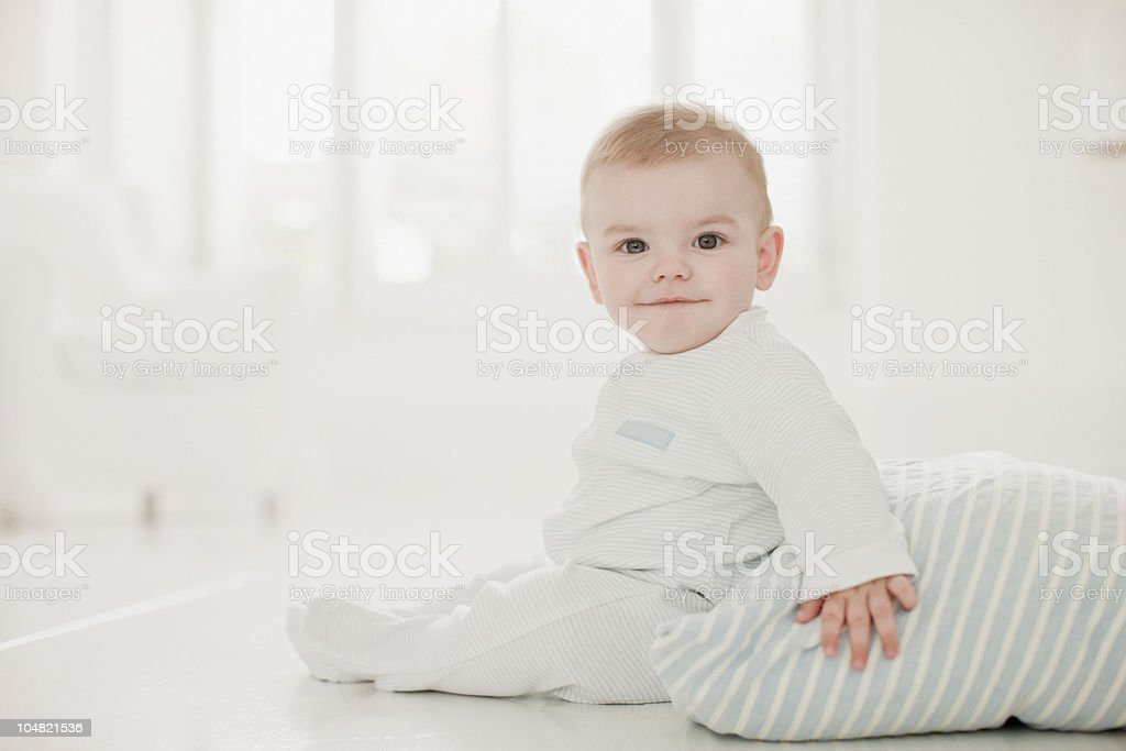 Smiling baby on floor with pillow royalty-free stock photo