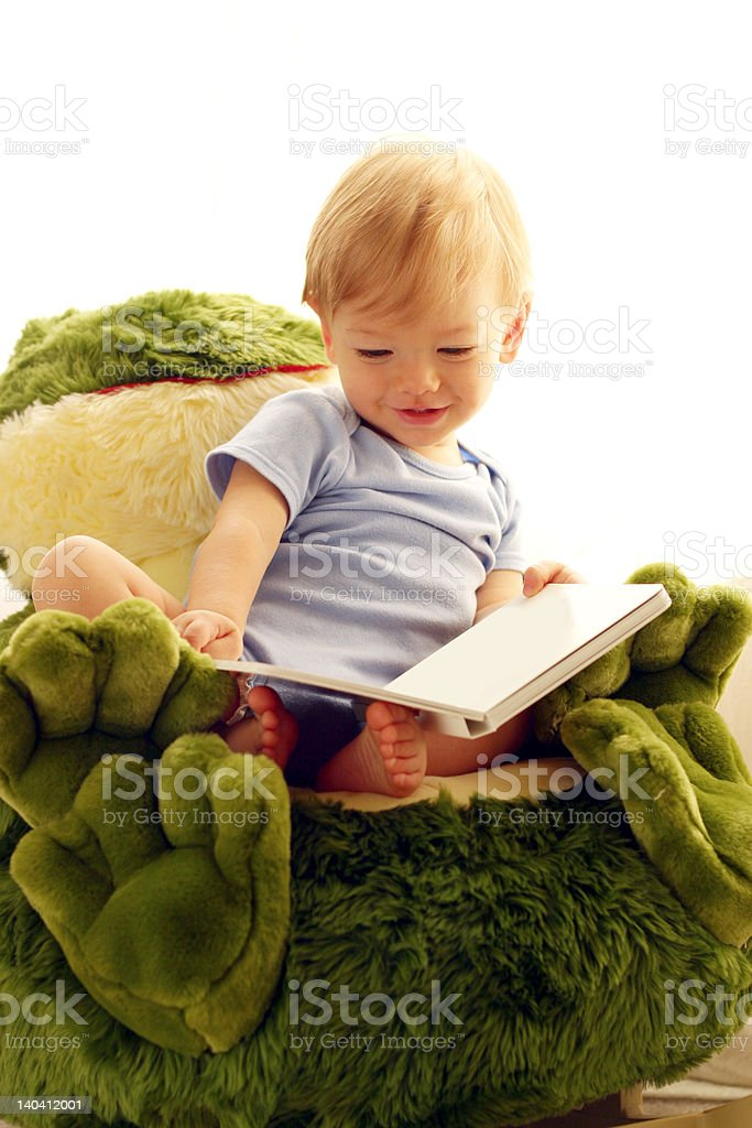 Smiling baby reading a book in frog chair royalty-free stock photo