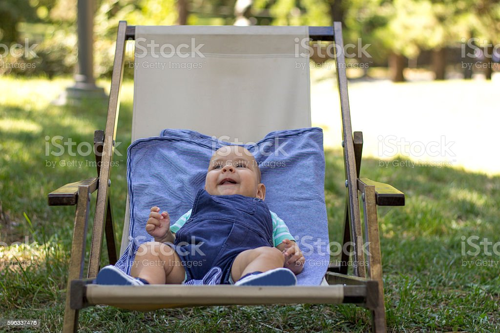 Smiling baby sit in outdoor textile chair. royalty-free stock photo