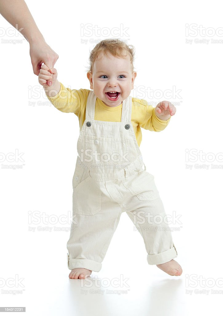 Smiling baby taking steps holding adult hand stock photo
