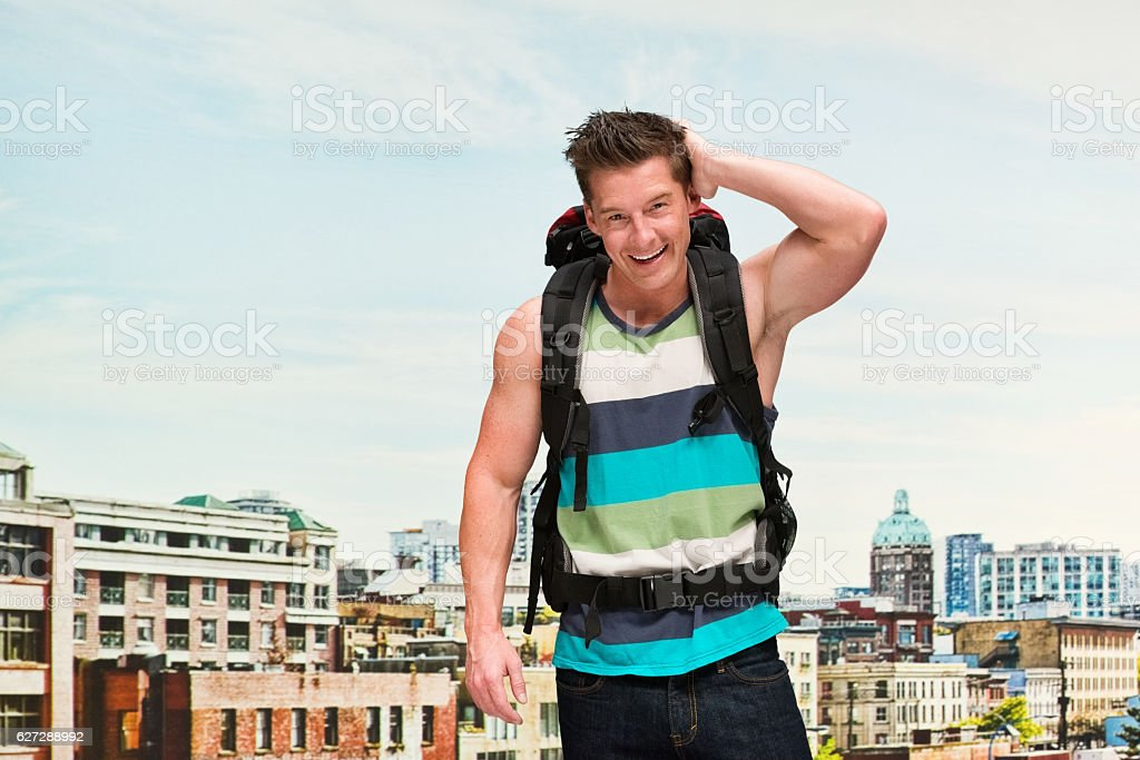 Smiling backpacker in front of city stock photo