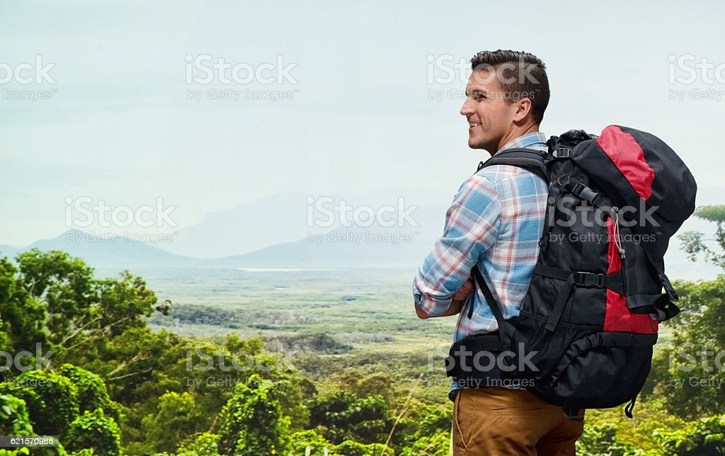 Smiling backpacker standing on mountain photo libre de droits