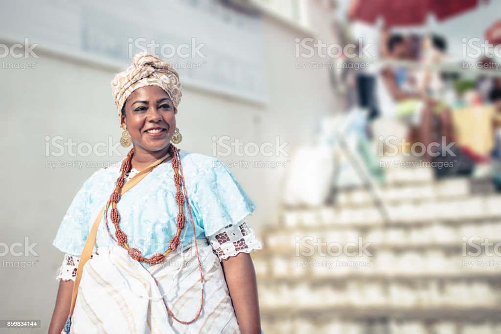 smiling baiana in traditional colorful costume in front of church in Salvador stock photo
