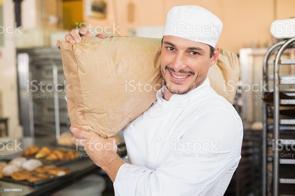 Smiling baker holding bag of flour stock photo