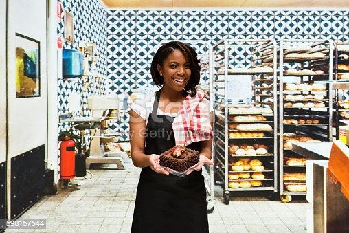 545282128 istock photo Smiling baker holding cake in bakery 598157544