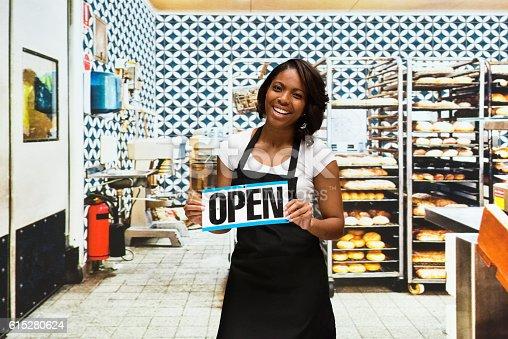 545282128 istock photo Smiling baker holding open sign in bakery 615280624