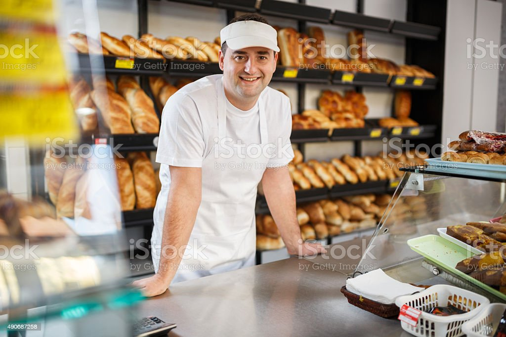 Smiling baker looking at camera in bakery. stock photo