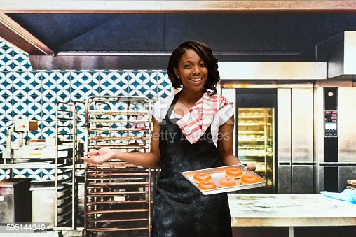 545282128 istock photo Smiling baker presenting in bakery 595144346