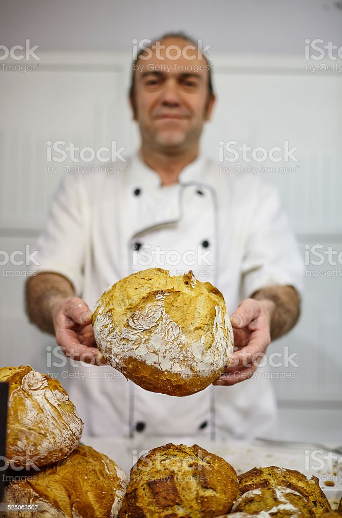 Smiling baker showing bread stock photo