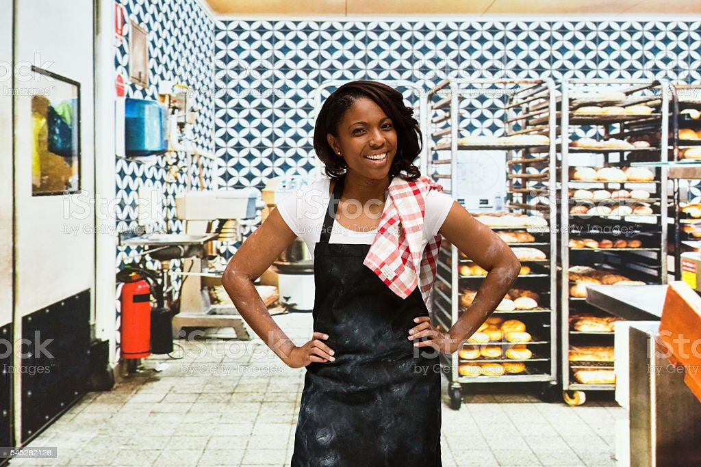 Smiling baker standing in bakery stock photo
