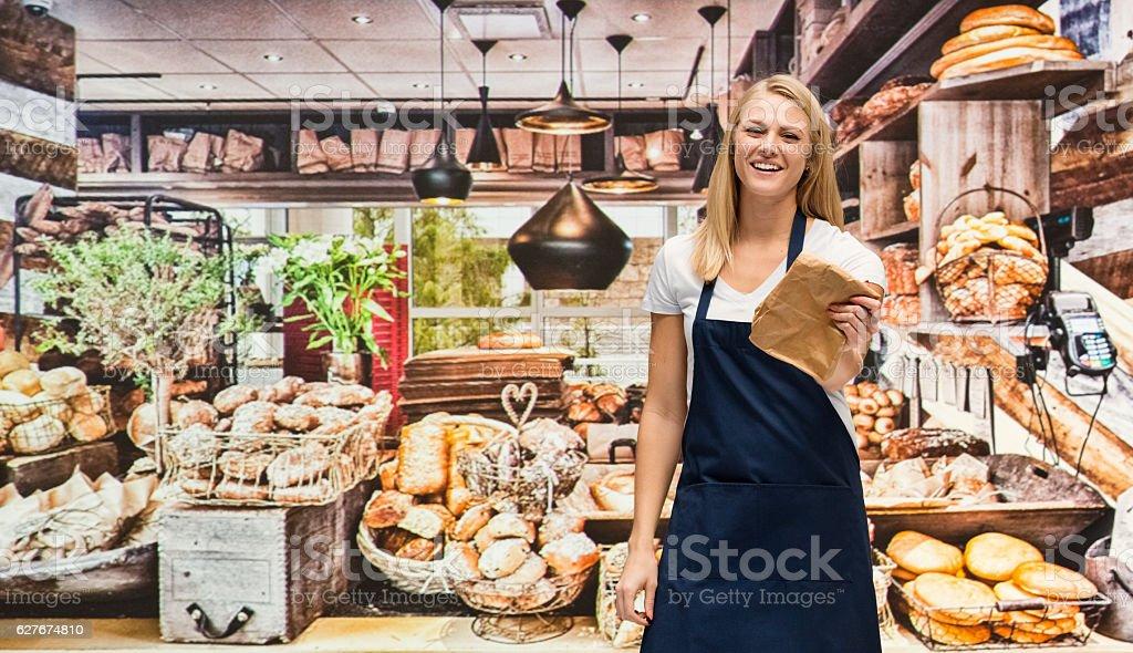 Smiling baker standing in bakery stock photo