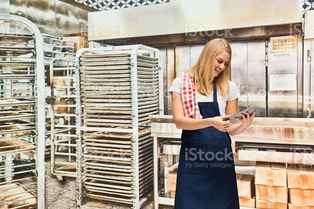 Smiling baker using tablet in bakery stock photo