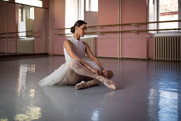 Smiling ballerina on the floor adjusting her ballet pumps. stock photo