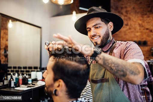 Smiling young hairdresser cutting customer's hair. Confident hipster barber is giving customer new hairstyle. They are at hair salon.