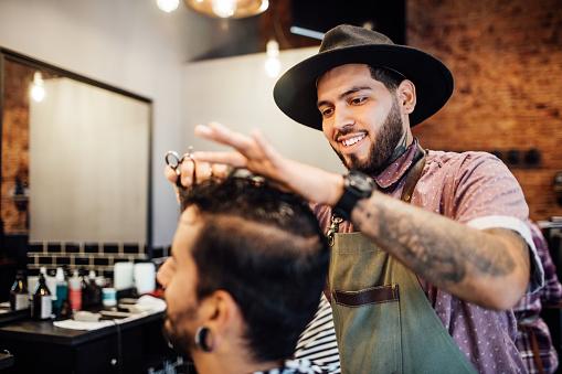 istock Smiling barber cutting customer's hair in salon 1030246848