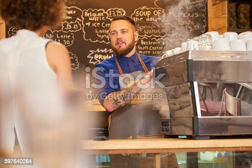 597640822istockphoto Smiling barista chatting to customer 597640264