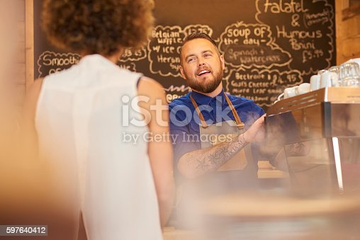 597640822 istock photo Smiling barista chatting to customer 597640412