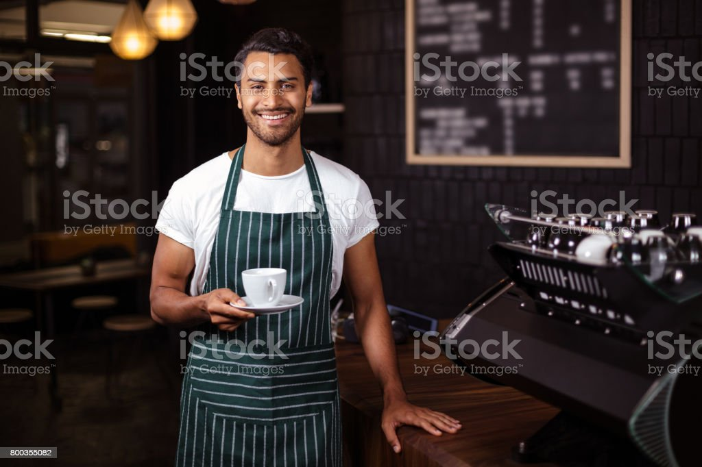 Smiling barista holding a cup of coffee stock photo