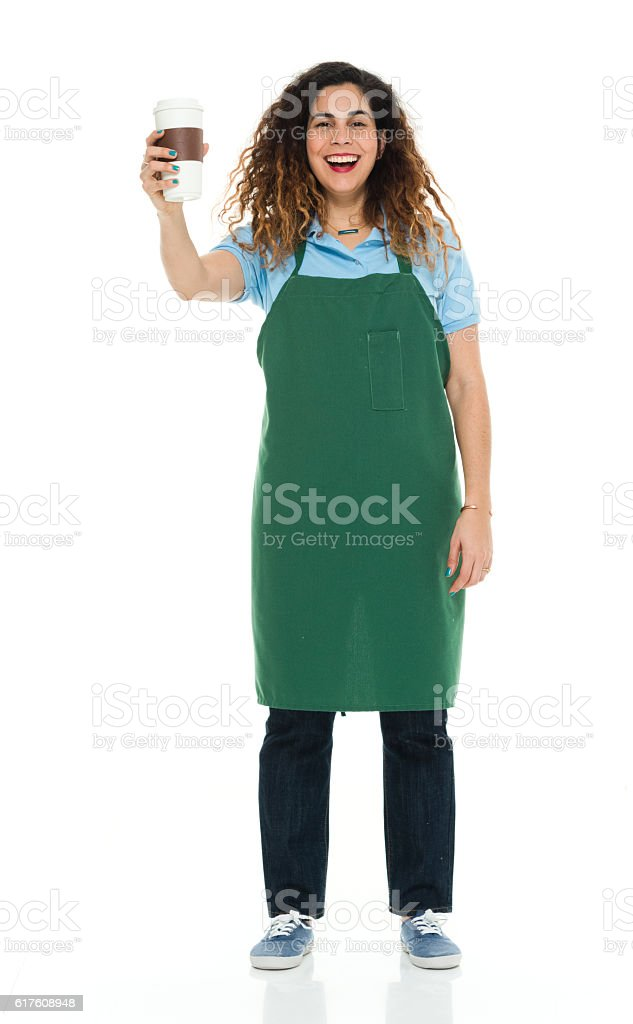 Smiling barista holding coffee cup stock photo