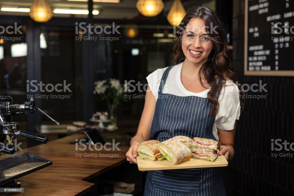 Smiling barista holding plate with sandwich stock photo