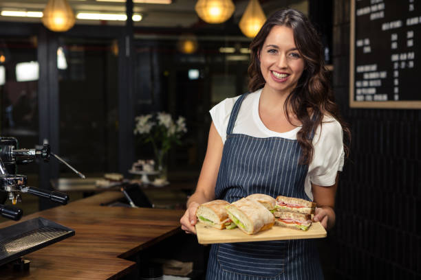 Smiling barista holding plate with sandwich Smiling barista holding plate with sandwich at coffee shop female sandwich stock pictures, royalty-free photos & images