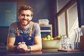 Portrait of smiling barista leaning on counter. Happy attractive male is in cafe. Waiter is wearing apron in coffee shop.