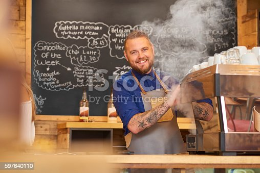 597640822istockphoto Smiling barista making coffee 597640110