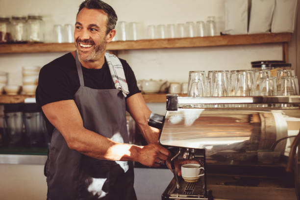 Smiling barista making espresso with a coffee maker stock photo