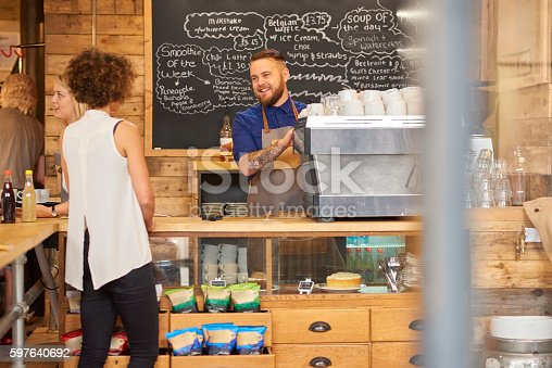 597640822 istock photo Smiling barista serving customer 597640692