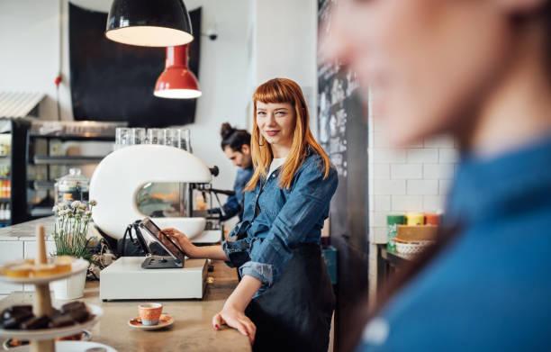 lächelnd am tresen im café barista stehen - stoffe berlin stock-fotos und bilder