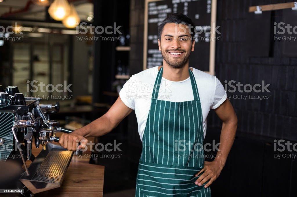 Smiling barista standing next coffee machine stock photo