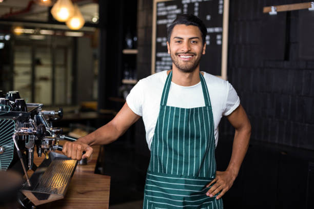 Smiling barista standing next coffee machine stock photo
