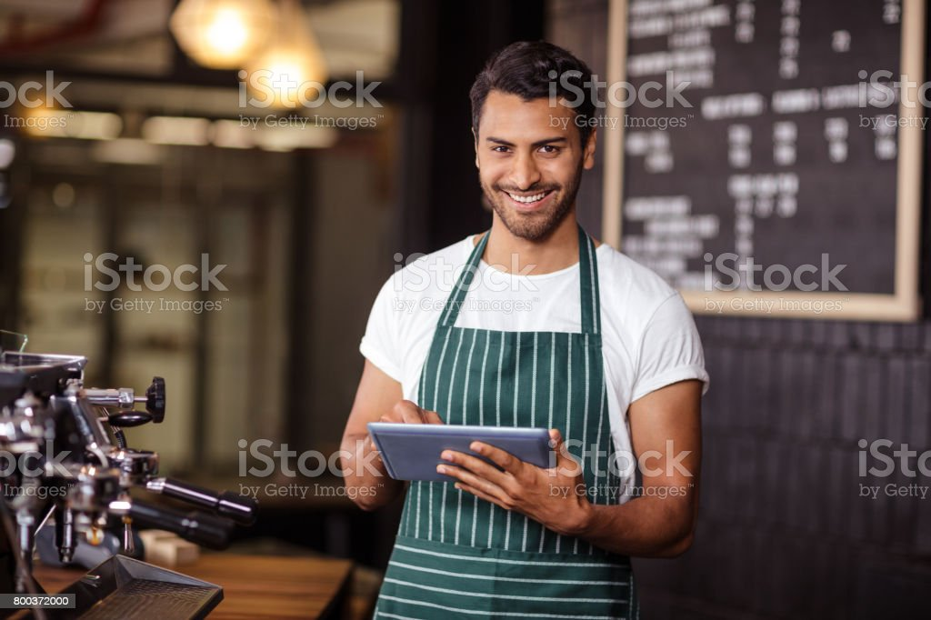 Smiling barista using tablet and looking at the camera stock photo
