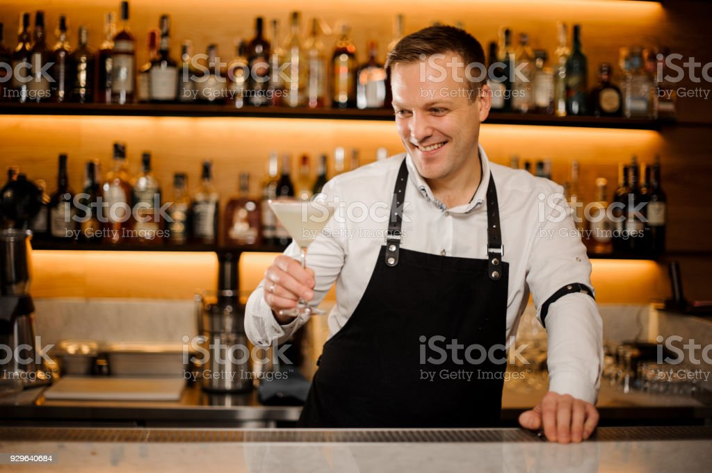 Smiling barman holding a cocktail glass with fresh alcoholic drink stock photo
