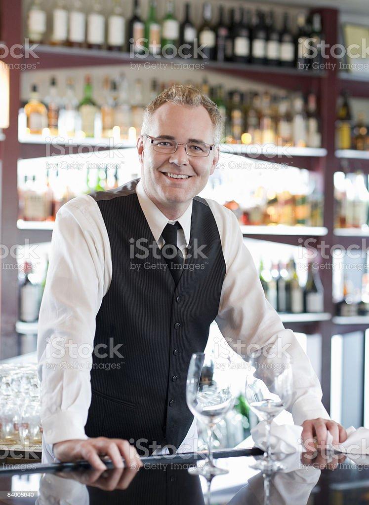 Smiling bartender behind bar. royalty-free stock photo