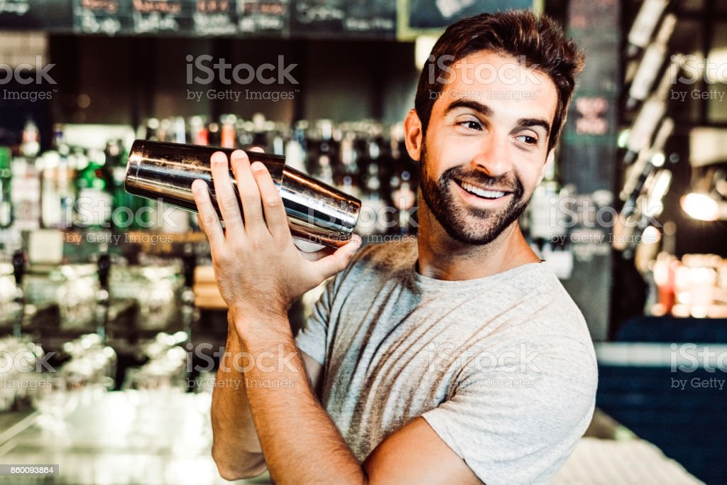 Lächelnde Barkeeper mixen Getränke im Shaker in bar – Foto