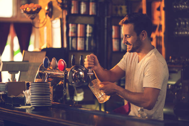 Smiling bartender pouring beer from beer tap in a bar. stock photo